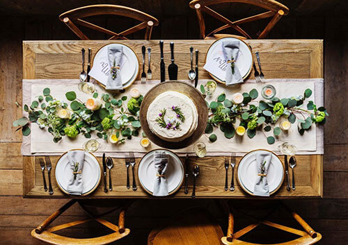 a wooden dining table set with plates