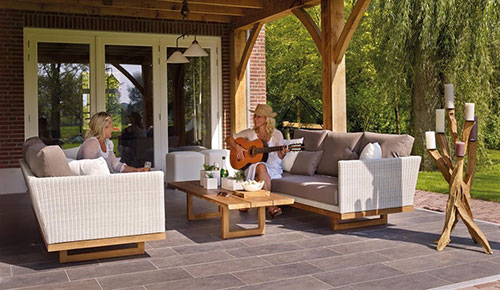 two women sitting on sofas on a furnished patio, one woman is playing guitar
