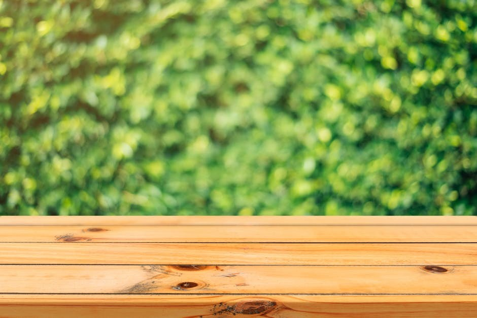 top of a wooden bench with blurred hedge in the background